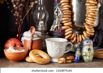 Traditional Russian Tea Party including hot black tea from samovar, lump sugar, crunch bagels sushki and baranki. Decoration with russian doll Matryoshka on wooden background