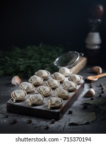 Traditional russian uncooked pelmeni on concrete background, dark food photo