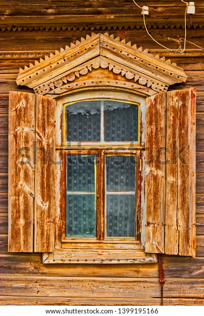 Traditional russian wooden window with open shatters in warm wooden tones