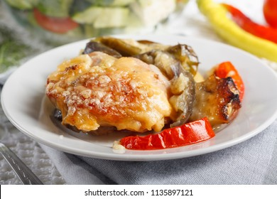 Traditional rustic stew of chicken and vegetables on plate with tomatoes, peppers and black olives