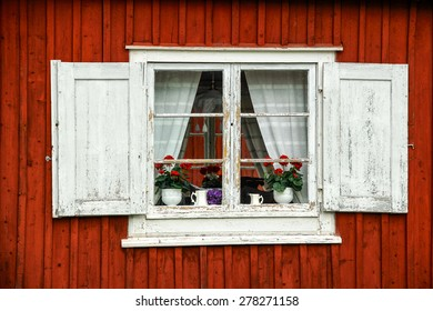 Traditional rustic white window on a red wooden wall, Sweden