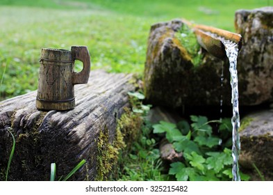 Traditional rustic wooden cup near clear water spring