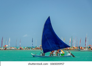 Traditional sailing boat (jangada) takes the tourists on a tour to see the corals on the beautiful beach of Pajucara, with turquoise blue clear water. Maceio, Alagoas, Brazil.