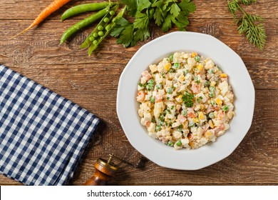 Traditional salad with cooked vegetables with mayonnaise. Wooden background. Top view.