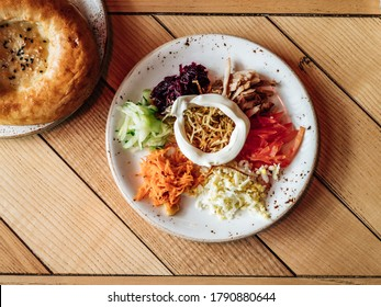 Traditional salad Moon in Yerevan or Yerevan Moon. Authentic shot of Armenian cuisine style salad with beaf, carrot, cucumber, eggs, beets, tomato on rustic wooden tabletop.