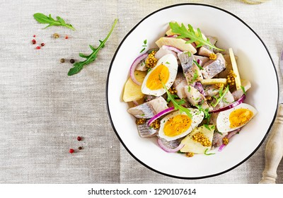Traditional  salad of salted herring fillet, fresh apples,  red onion  and eggs. Kosher food. Scandinavian cuisine. Top view. Flat lay