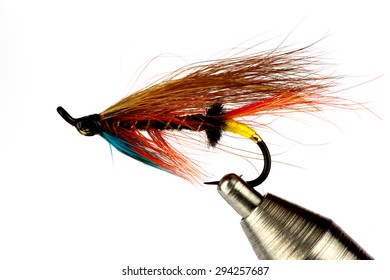 A Traditional Salmon Fly Held In A Fly Tying Vise Isolated on a White Background