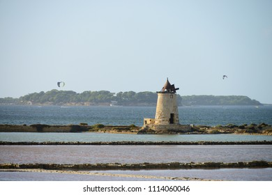Traditional salt manufacturing windmill with kite surfer in the background, Saline di Trapani, Sicily, Italy