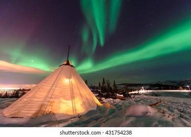 Traditional Sami reindeer-skin tents (lappish yurts) in Troms region of Norway .The polar lights in Norway .