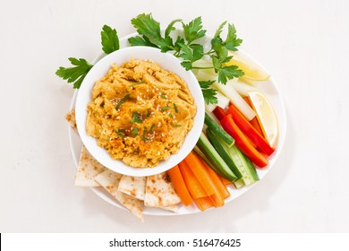 traditional sauce hummus with fresh vegetables and pita bread, top view, horizontal