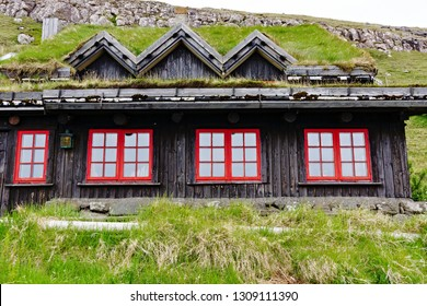 Traditional scandinavian house with grass roof and red windows on Faroe islands