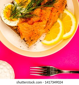 Traditional Scandinavian Style Open Face Fresh Smoked Salmon Sandwich, With Hard Boiled Eggs On Rye Bread With Dill And Lemon, On A Pink Background With No People
