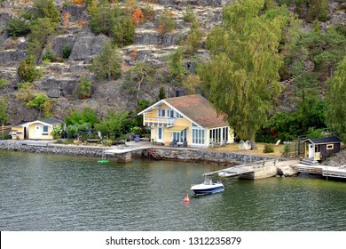 Traditional scandinavian wooden house on rocky shore of Baltic Sea
