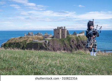 Traditional scottish bagpiper in full dress code at Dunnottar Castle in Stonehaven
