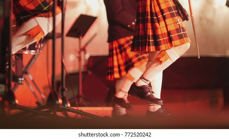 Traditional scottish band musicians singing with bagpipes and drums on the stage