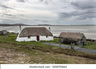 A traditional Scottish Hebridean thatched cottage c1750 and storehouse. Roof held in position with ropes weighted down with stones. Located by the sea on the island of North Uist in the Outer Hebrides