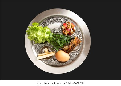 Traditional seder, holiday dinner on the occasion of Passover. Seder plate isolated on a black background.