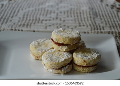 Traditional Serbian homemade powdered sugar vanilla cookies with jam(vanilice) on the white square plate and crochet lace grandma´s  tablecloth.