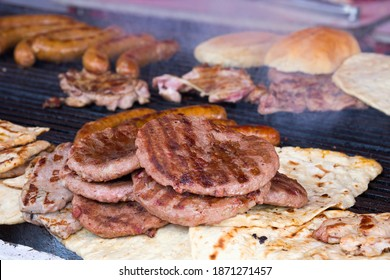 Traditional serbian street food (rostilj) - pljeskavica, cevapi, grilled chicken breast, bbq chicken wings and homemade sausages served with fresh bakery (lepinja)