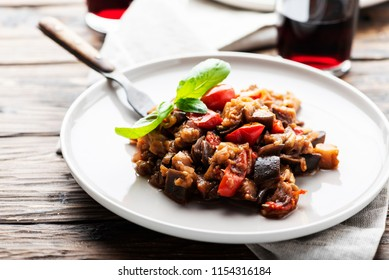 Traditional sicilan eggplant dish caponata on the wooden table, selective focus