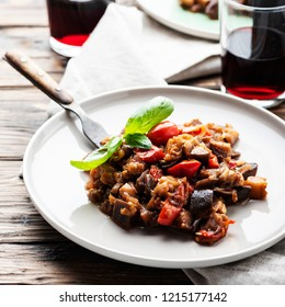 Traditional sicilan eggplant dish caponata on the wooden table, selective focus and square image