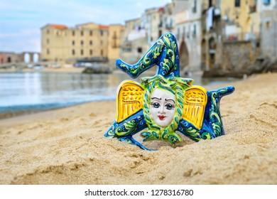 Traditional sicilian souvenir - ceramic Thrinacia on a sandy beach in Cefalu. Sicily, Italy