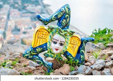 Traditional sicilian souvenir - ceramic Thrinacia on a cliff above Cefalu. Sicily, Italy