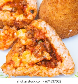 traditional sicilian street food - open meat ragu stuffed rice balls arancini on plate