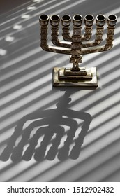 Traditional silver jewish menorah on a white background with stripes of shadow from the blinds