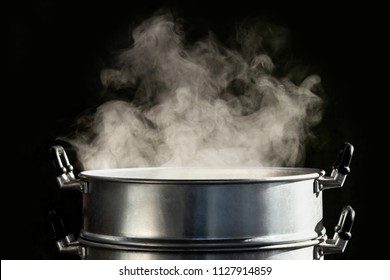 Traditional silver steamer pot with white smoke while cooking on black background