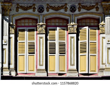 Traditional Singapore Peranakan or Straits Chinese shop house with original wooden shutters and inset Chinese tiles in historic Geylang