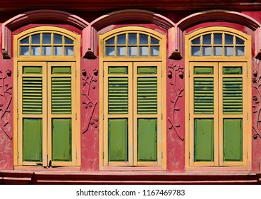 Traditional Singapore Peranakan or Straits Chinese shop house with arched windows and green shutters in historic Geylang