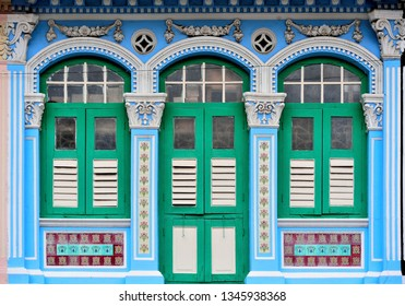 Traditional Singapore Peranakan or Straits Chinese shop house with arched windows, blue exterior and antique green and white wooden shutters in downtown Singapore