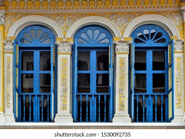 Traditional Singapore shop house with striking blue and white facade and arched windows with antique wooden shutters in historic Bugis, Singapore.