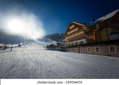 Traditional ski resort at Austrian Alps with working snow cannons at sunny day
