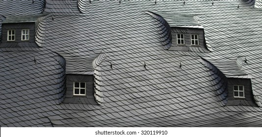 Traditional slate / shale tiles roof with attic windows in a concept of 'different points of view'. Picturesque fragment of a typical apartment house built in the 16th century. Harz region, Germany.