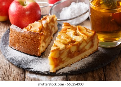 Traditional sliced apple pie close-up on a table and juice. horizontal