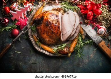 Traditional sliced roasted glazed Christmas ham with holiday festive decoration on dark rustic background, top view, border