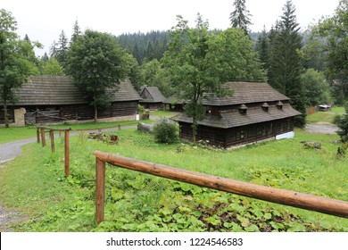 Traditional Slovakian wooden houses on old street with wooden fence in Open Air Museum of ancestry village in Slovakia, Zuberec