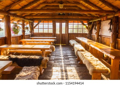 Traditional Slovakian Wooden Interior of Building Extension Used for Dining. Classic Sheep Pads on Sitting Benches.  Light Coming Through the Door.