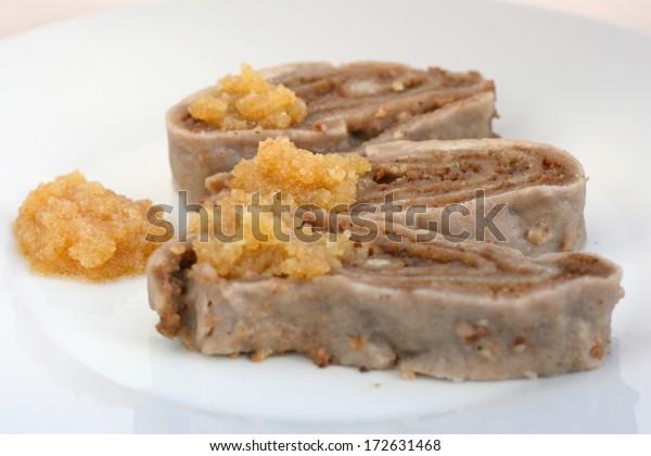 伝統的なスロベニア料理:アジドビ・ストルクルジ – 蕎麦粉を使い、クルミや蜂蜜を入れたロールケーキを湯で煮たもの。通常、茶色のバターパン粉を添えて供される