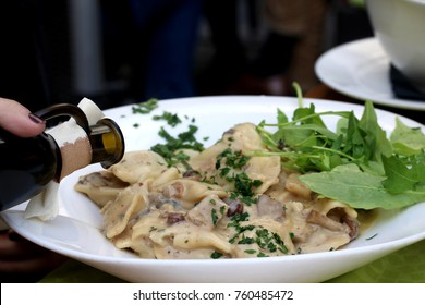Traditional Slovenian meal called 'Idrijski zlikrofi' - dumplings made from dough with potato filling, served with bacon and mushroom sauce. Selective focus.