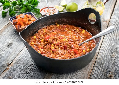 Traditional slow cooked Mexican chili con cane with mincemeat, beans and corn as closeup in a modern design cast-iron roasting dish