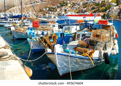 traditional small fishing boats docked in the main port of Symi island in Greece