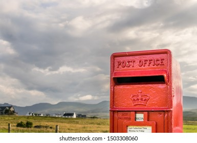 Traditional small red British post box.