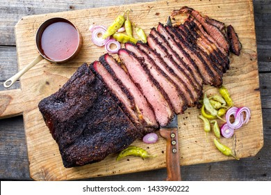 Traditional smoked barbecue wagyu beef brisket offered as top view on an old cutting board with Louisiana sauce onion rings and peperoni