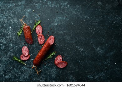 Traditional smoked salami sausage with spices. Slice sausages. Rosemary. Top view. Free space for your text.