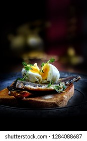 Traditional smoked Scottish kippers on toast with poached egg and thyme herb garnish. Shot against a dark, rustic background with copy space.