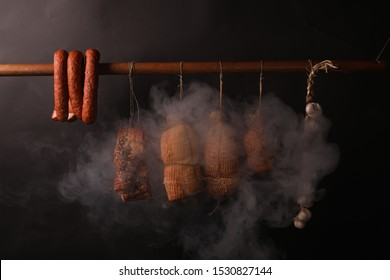 Traditional smokehouse. Sausages, hams and bacon surrounded by smoke in a smokehouse.
