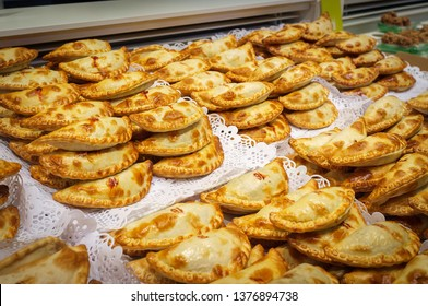 Traditional snack with tuna, an empanada is a type of pastry baked or fried in Hispanic cultures. Mix set empanadas (veg and meat) at La Boqueria market in Barcelona, Spain